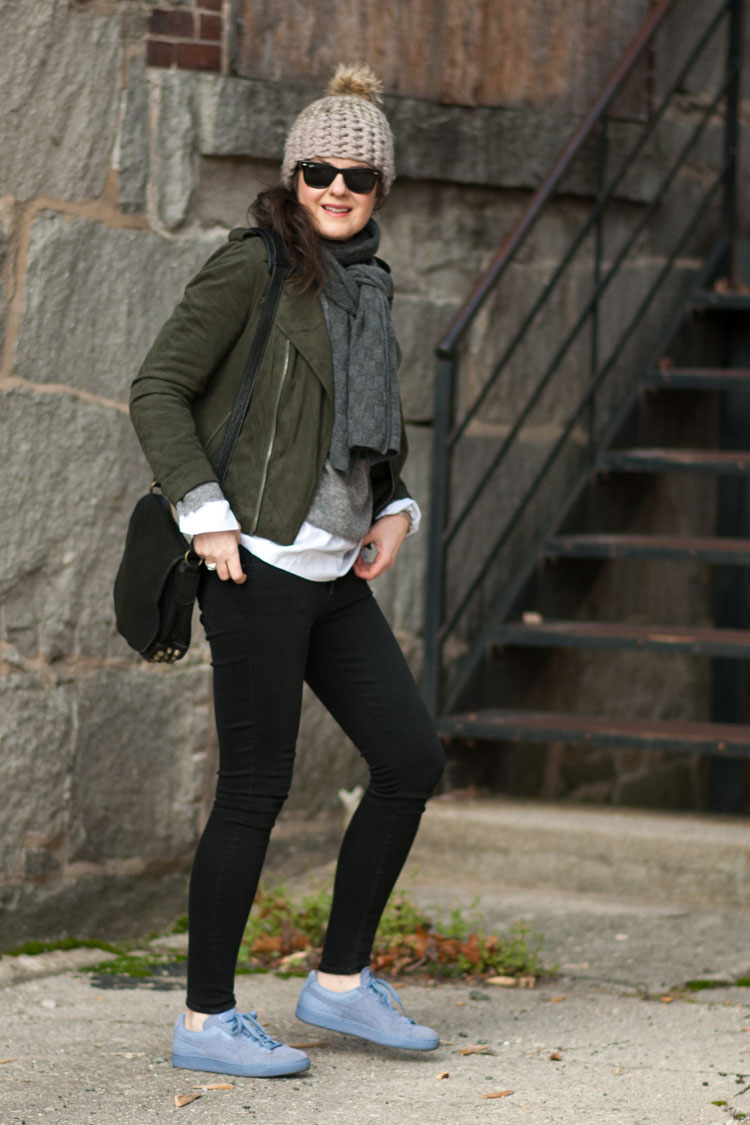 Street style blogger outfit with green suede moto jacket, black skinny jeans and purple sneakers